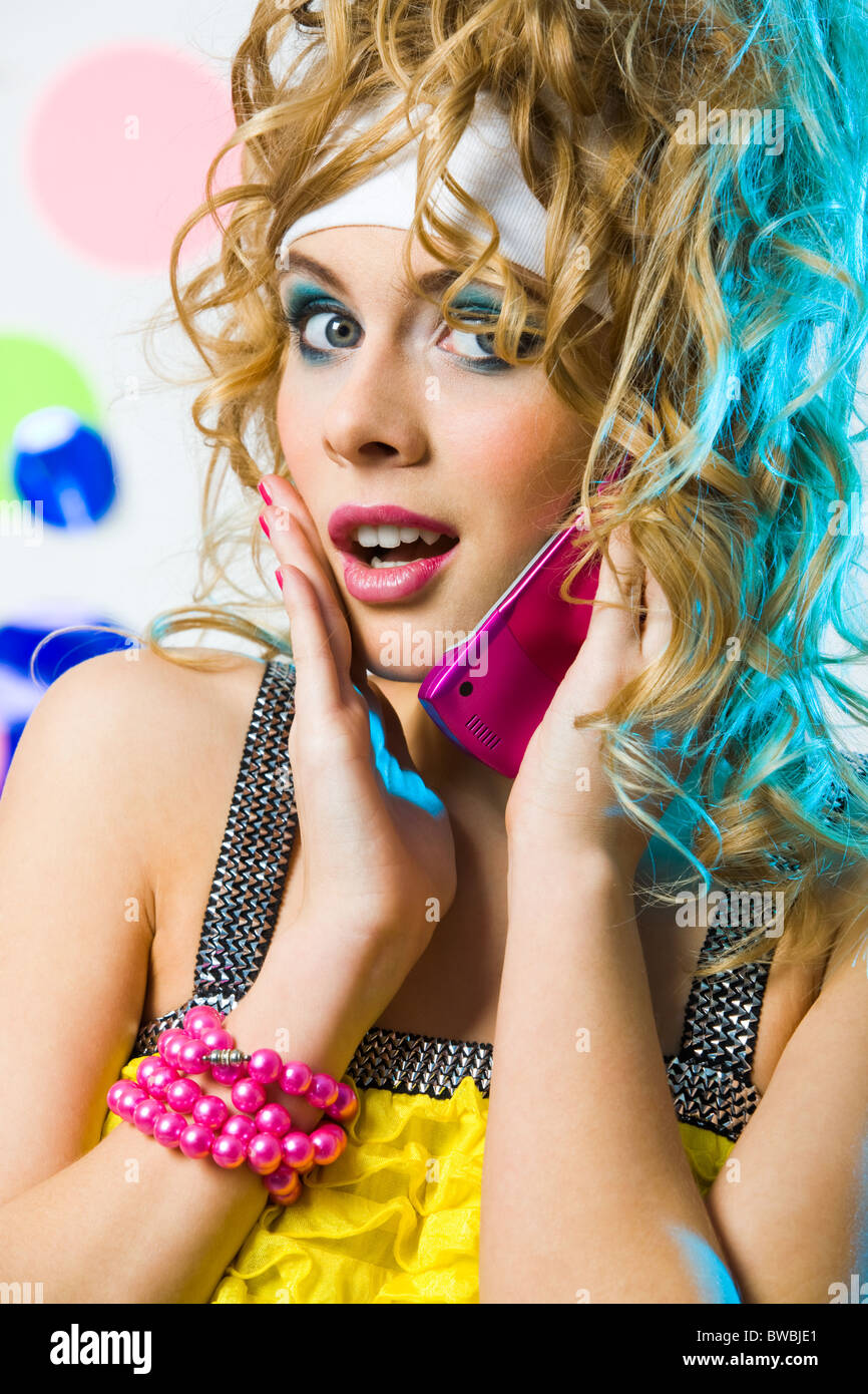 Photo of cute blonde with wavy hair talking on cellular phone and looking at camera surprisingly - Stock Image