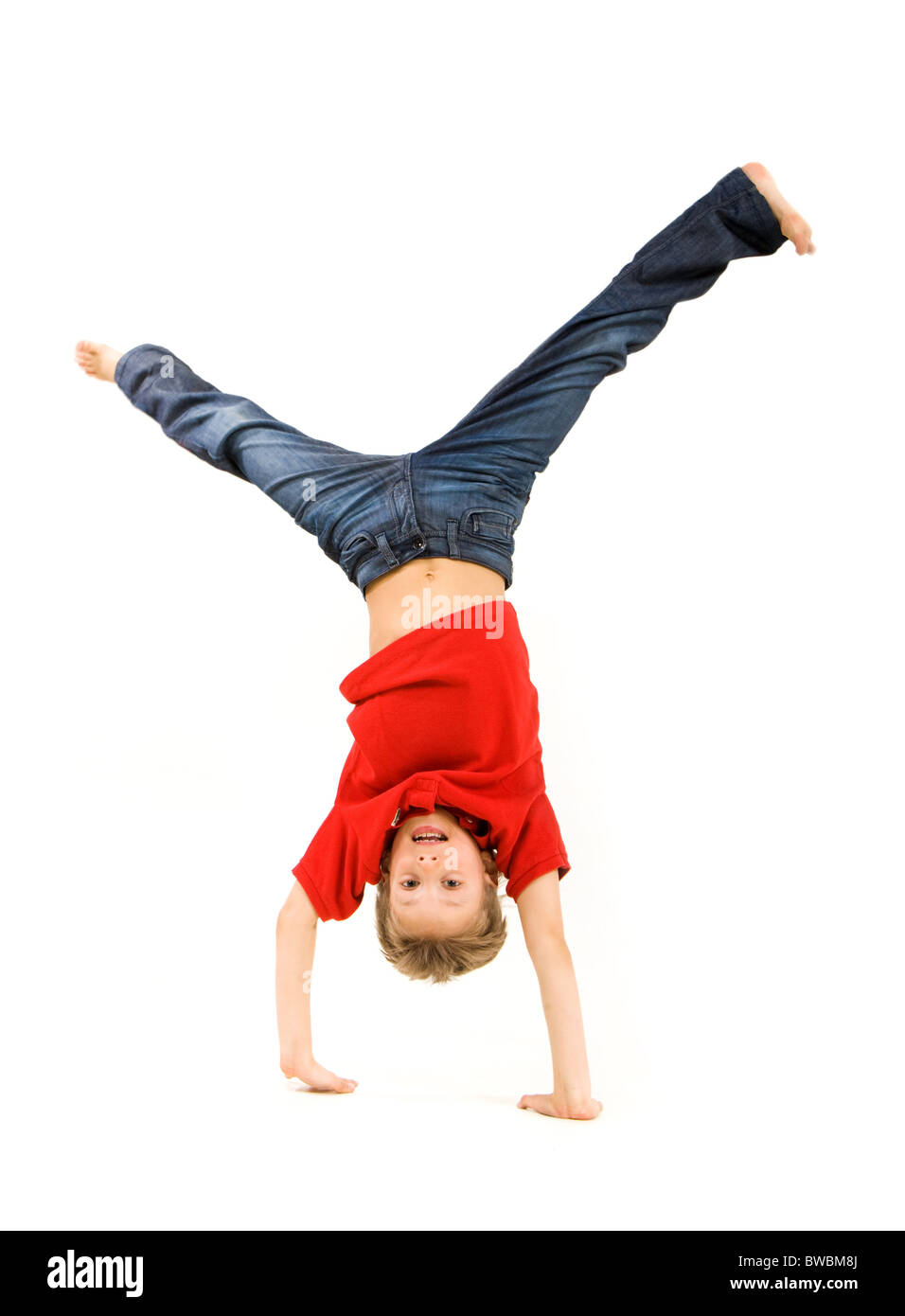 Playful lad standing on his arms with legs pointing upwards over white background - Stock Image