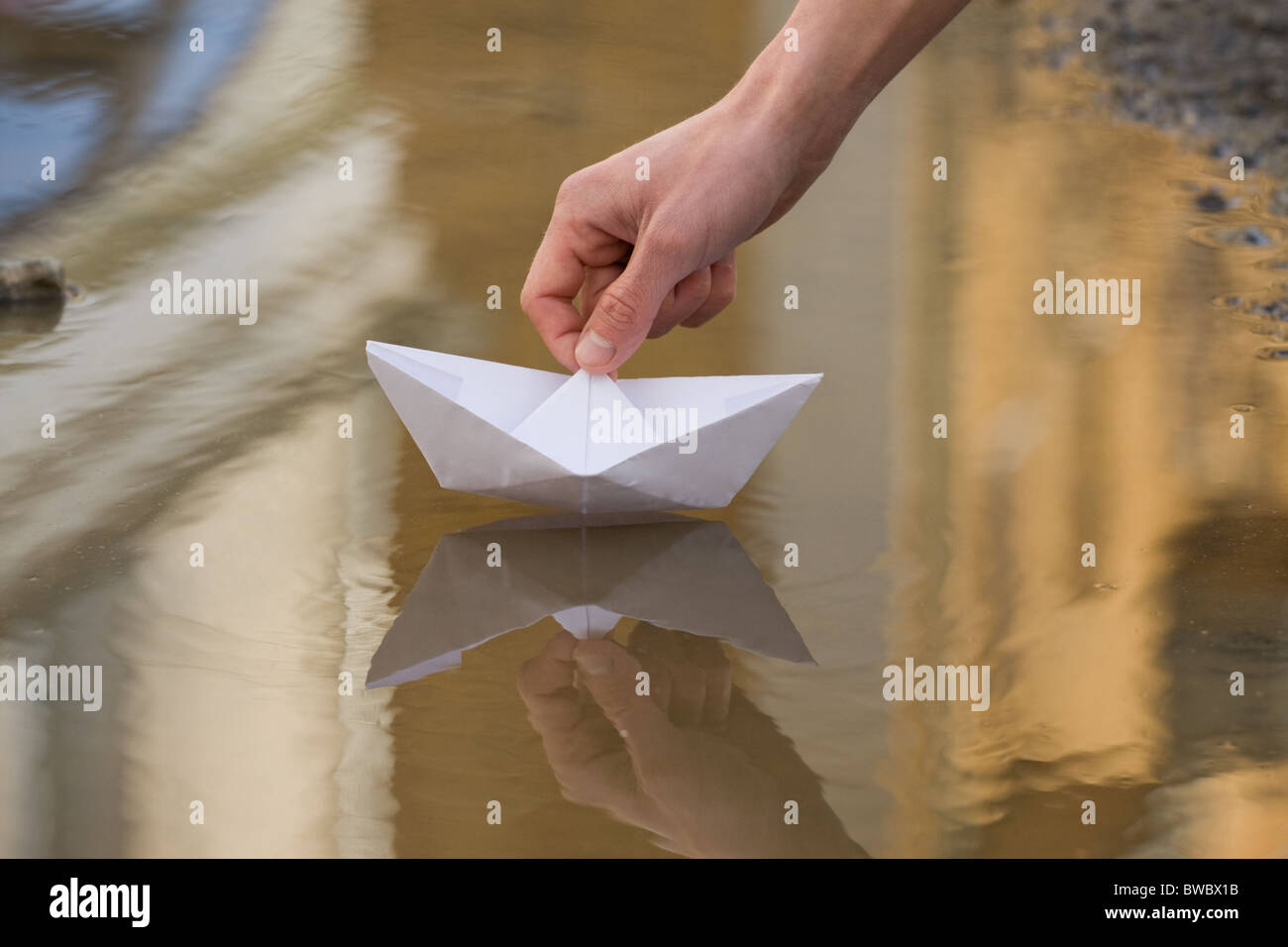 Close-up of human hand putting paper ship lying onto still water - Stock Image