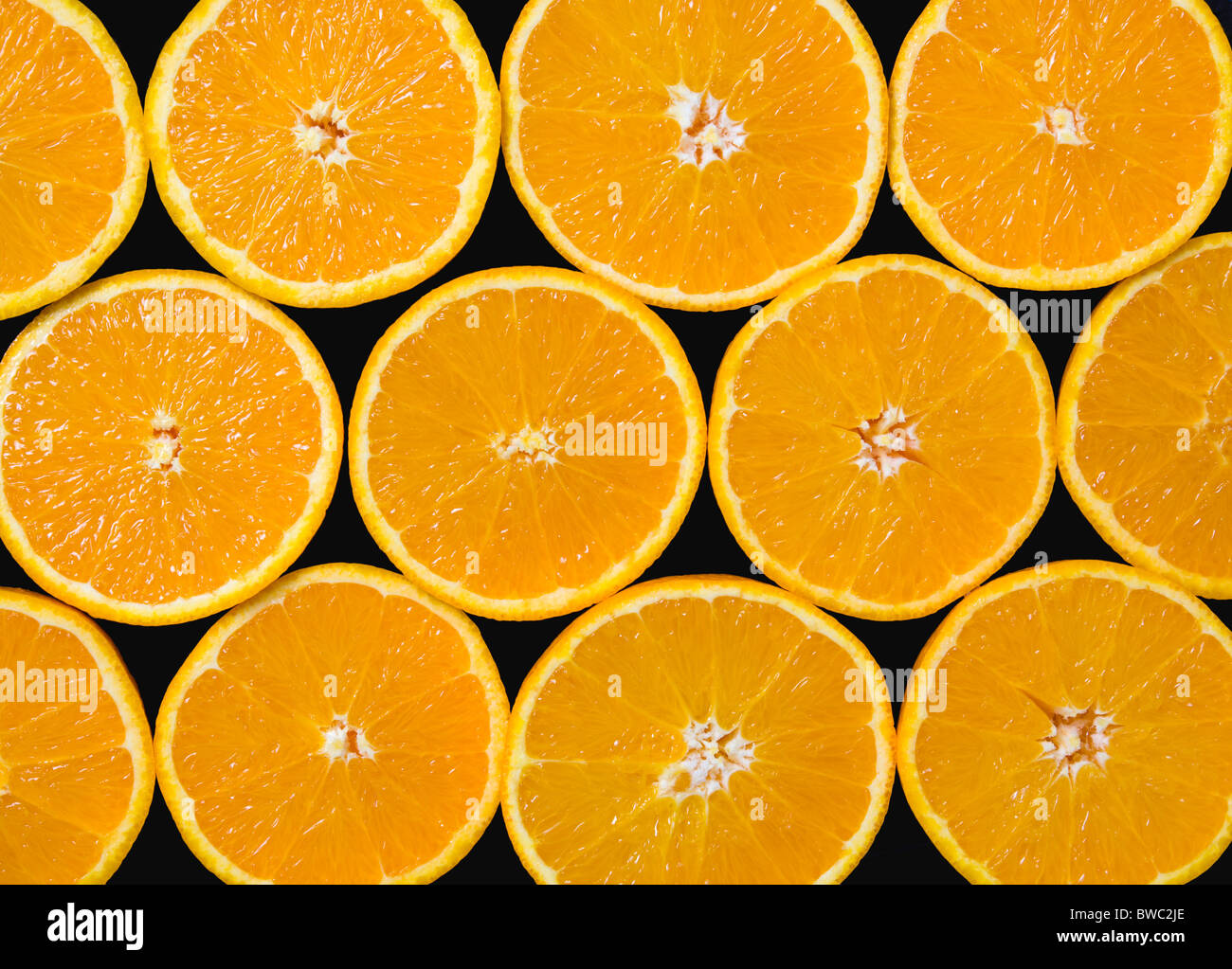 Food, Fruit, Oranges, Overhead view of group of oranges cut in half showing core and segments against a black background. - Stock Image