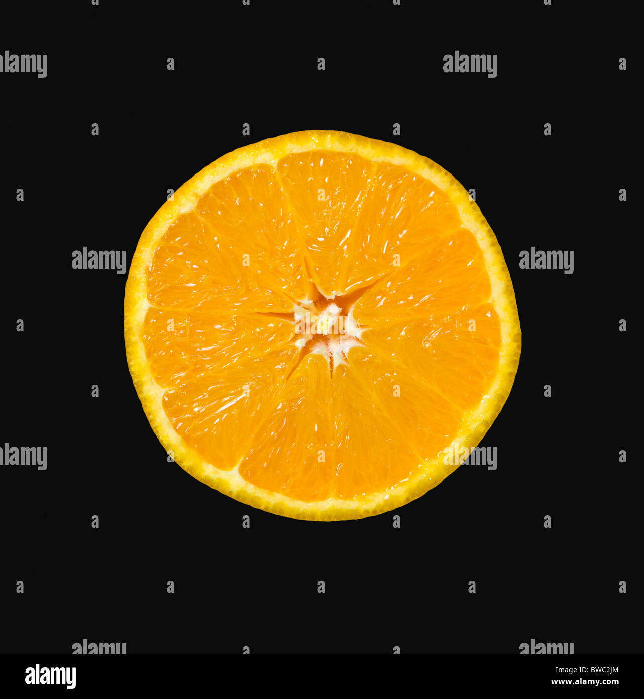 Food, Fruit, Oranges, One single ripe orange cut in half showing core and segments against a black background. - Stock Image