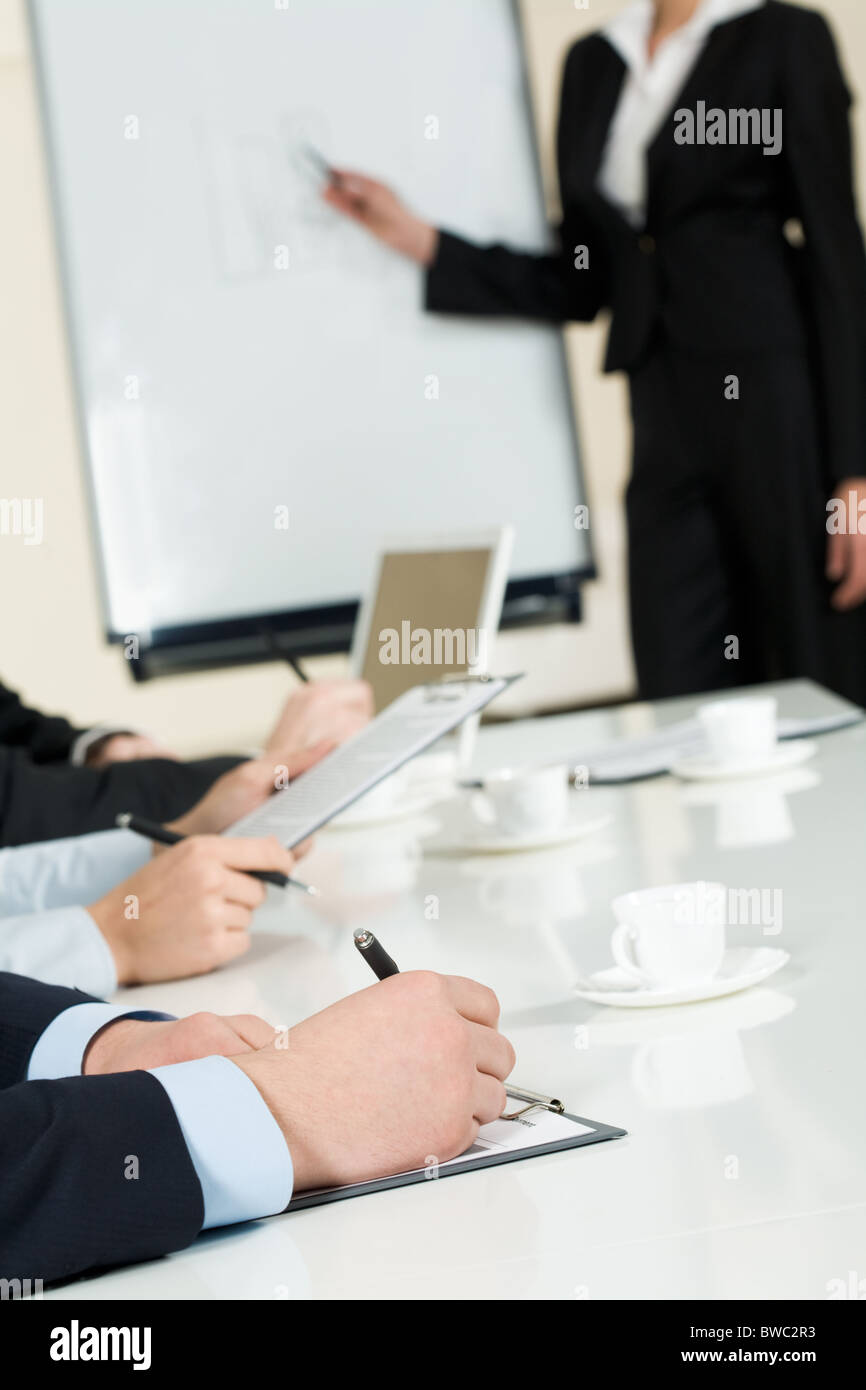 Image of human hands making notes on paper at seminar or conference - Stock Image