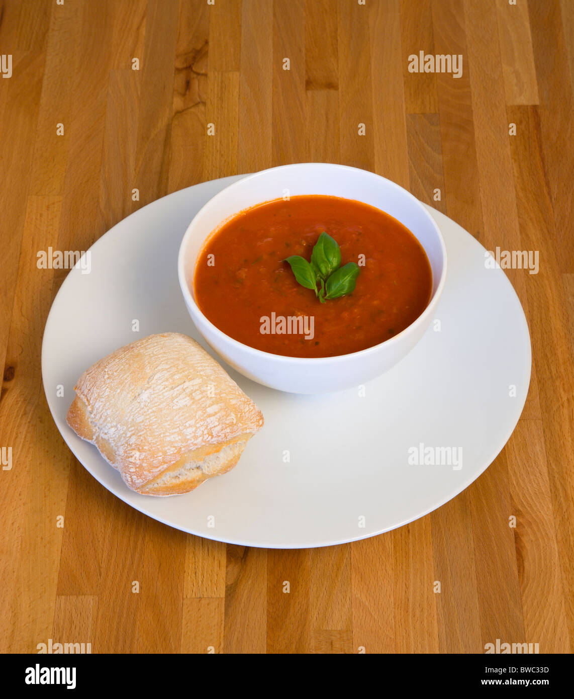 Food Cooked Soup Bowl of tomato and basil soup on a plate with a rustic bread roll on a wooden table surface. & Food Cooked Soup Bowl of tomato and basil soup on a plate with a ...