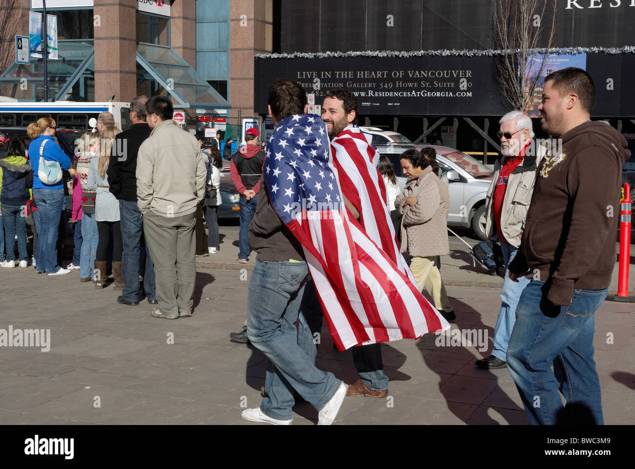 Two American patriots draped in American flags walk the streets of Vancouver. - Stock Image