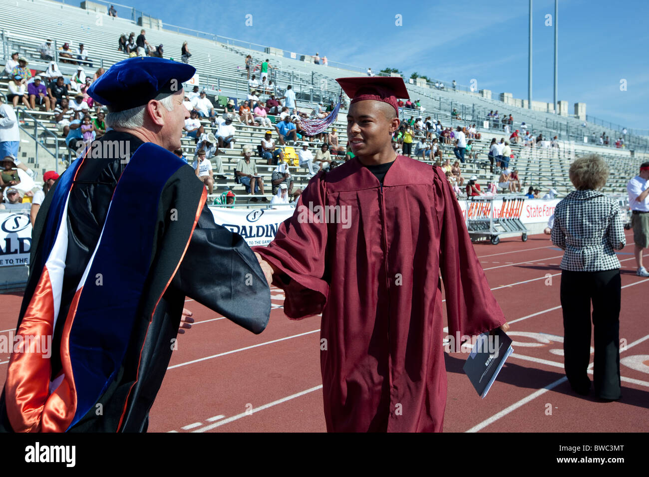 African-American student receives high school diploma from school official during outdoor graduation ceremony - Stock Image