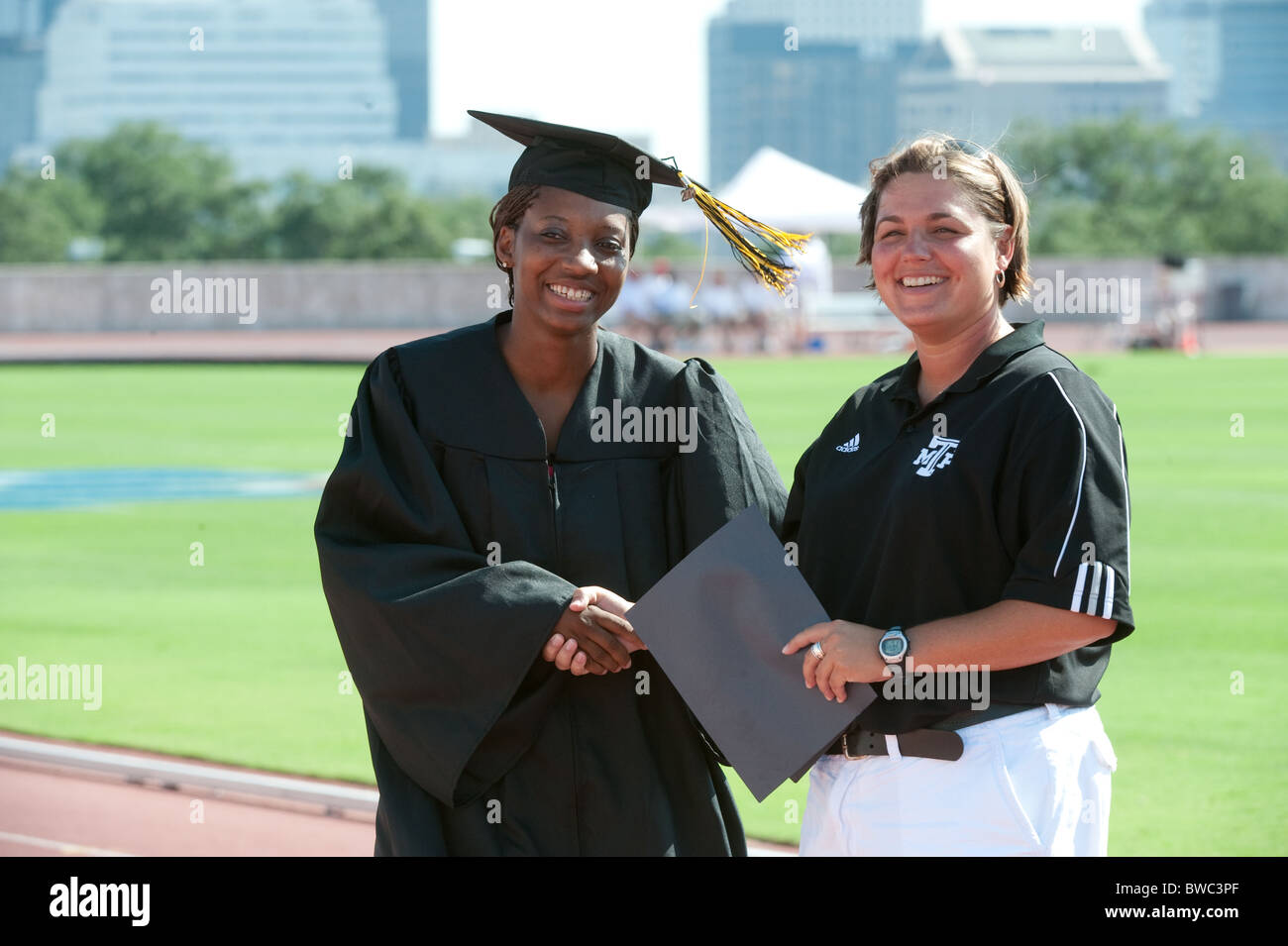 African-American female high school student receives diploma at an outdoor ceremony during track meet - Stock Image