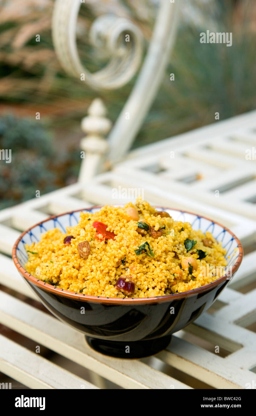 Food, Cooked, Pasta, Bowl of Moroccan couscous with fruit nuts and vegetables on a metal table in a garden. - Stock Image