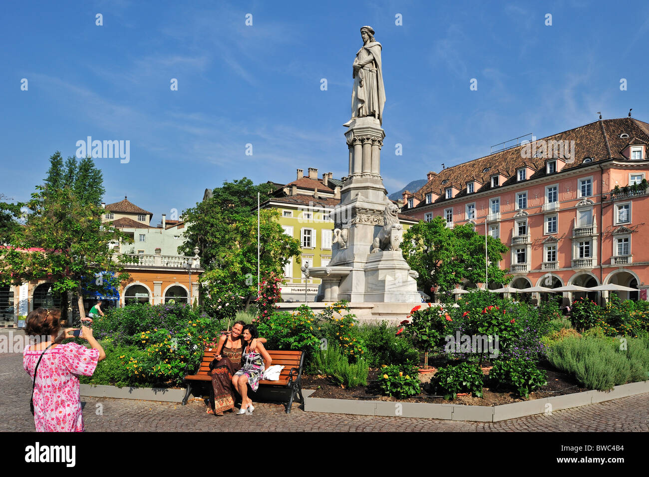 Tourists posing in front of statue of Walther von der Vogelweide at the Piazza Walther in Bolzano / Bozen, Dolomites, - Stock Image