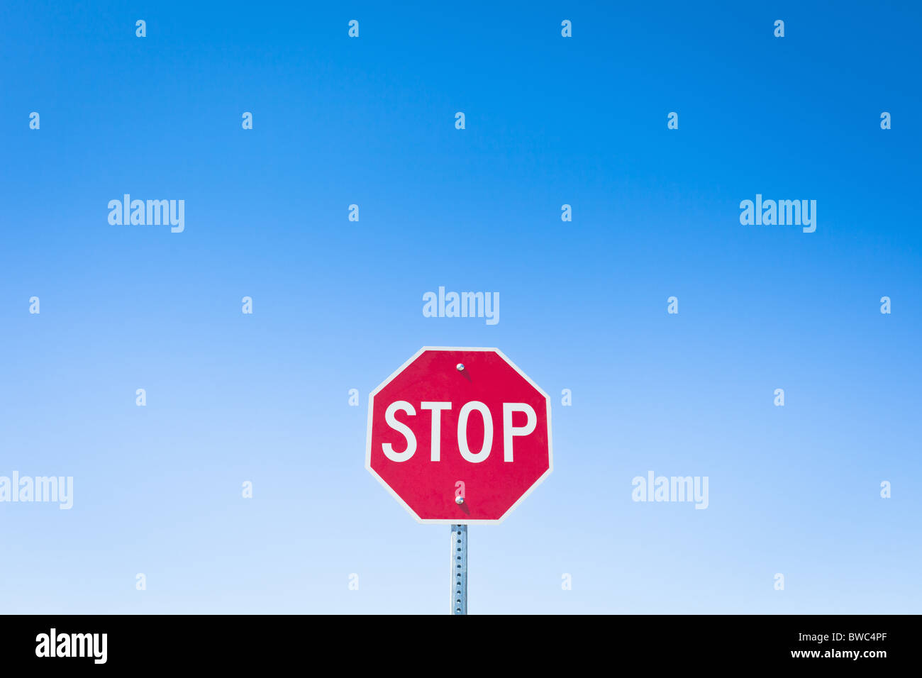 Stop sign against blue sky - Stock Image