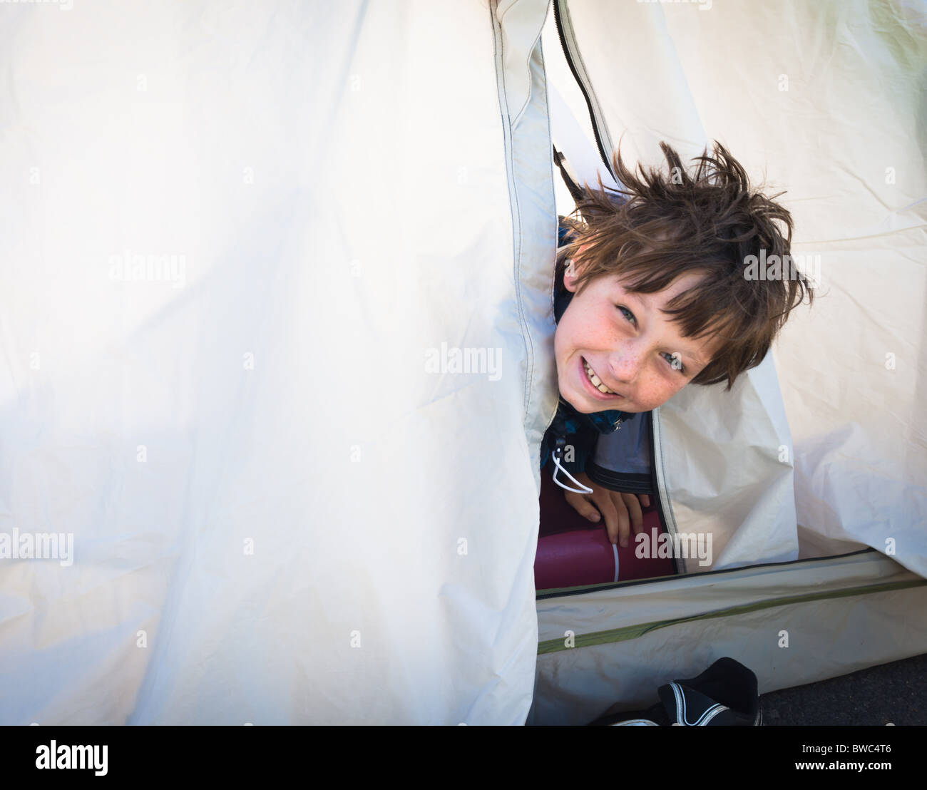 Boy looking out of tent - Stock Image