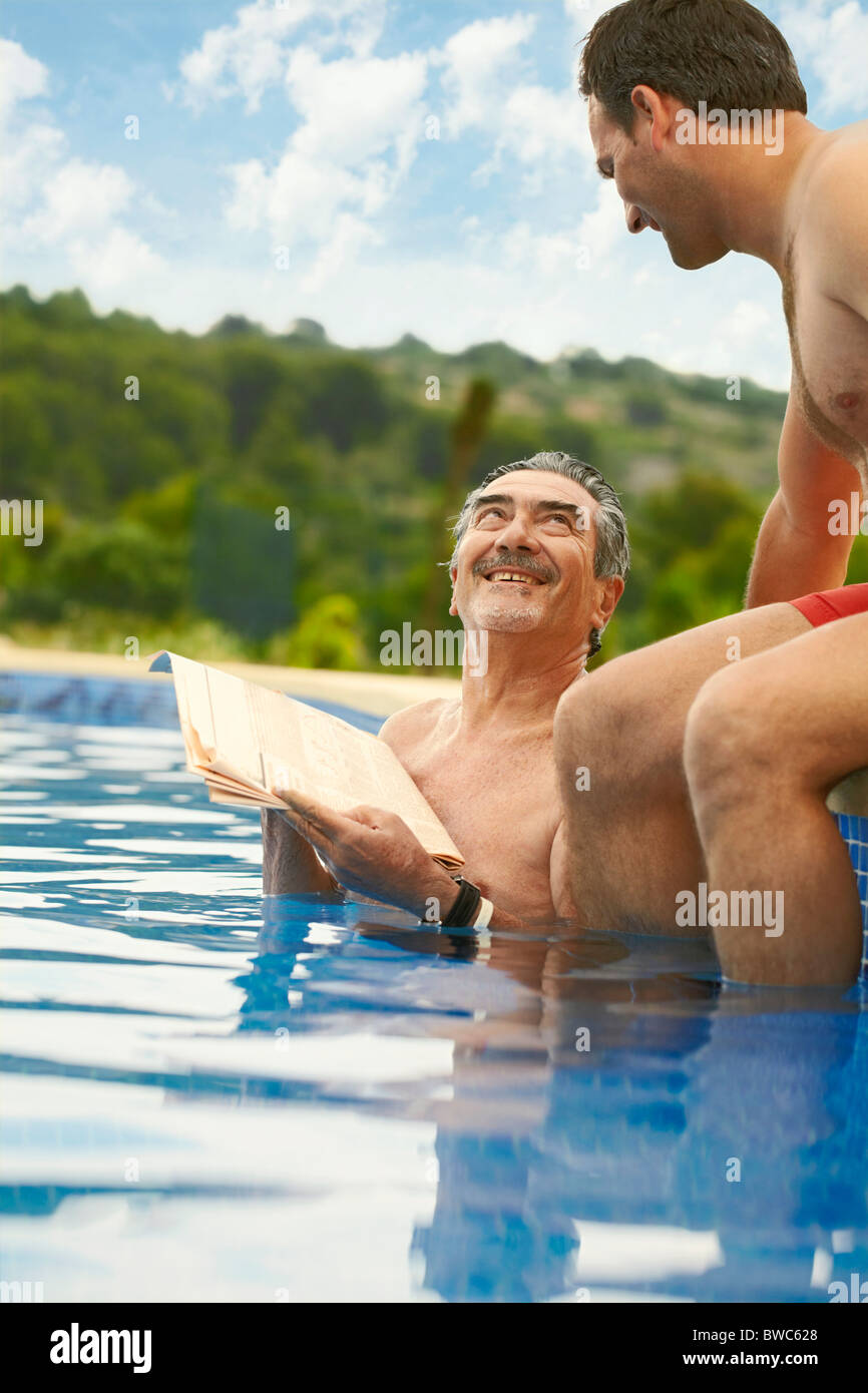 Older man reading news in swimming pool - Stock Image