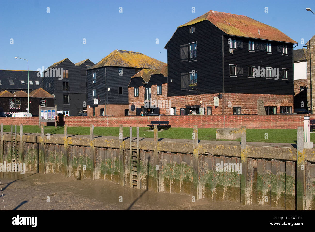 silted river bank  public access riverside lawn Georgian warehouses - Stock Image