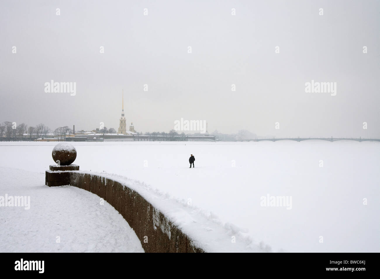 Man walking on the frozen Neva River, 'Peter and Paul Fortress' in background St Petersburg Russia - Stock Image