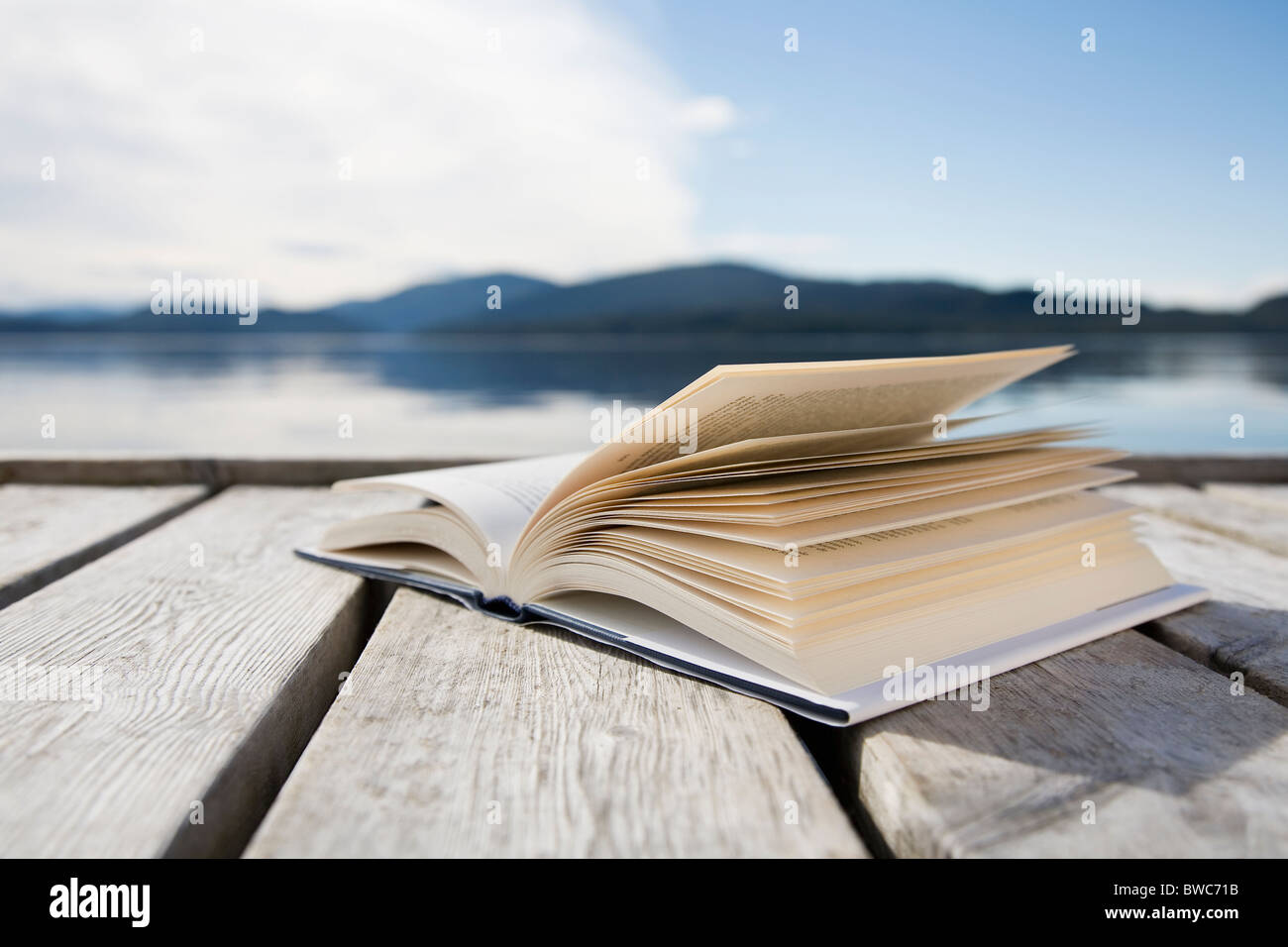 Book on jetty by sea and mountains - Stock Image