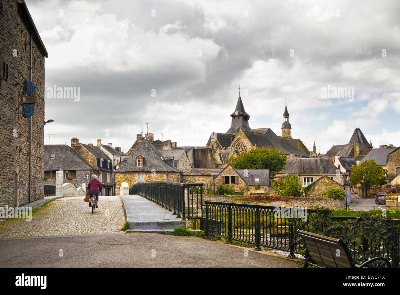 Woman cycling over the bridge at Malestroit, Morbihan, Brittany, France, Europe - Stock Image