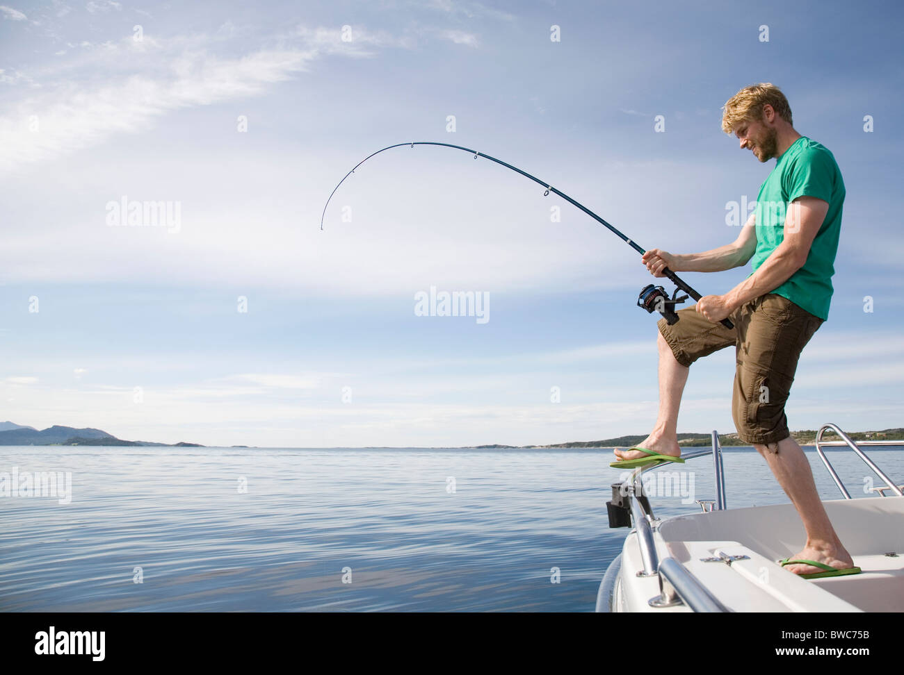 Man deep-sea fishing from boat - Stock Image