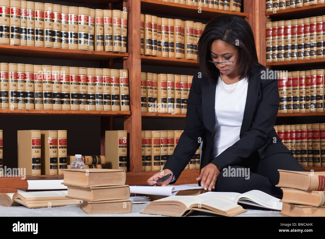 USA, California, Oakland, Woman reading books in library - Stock Image