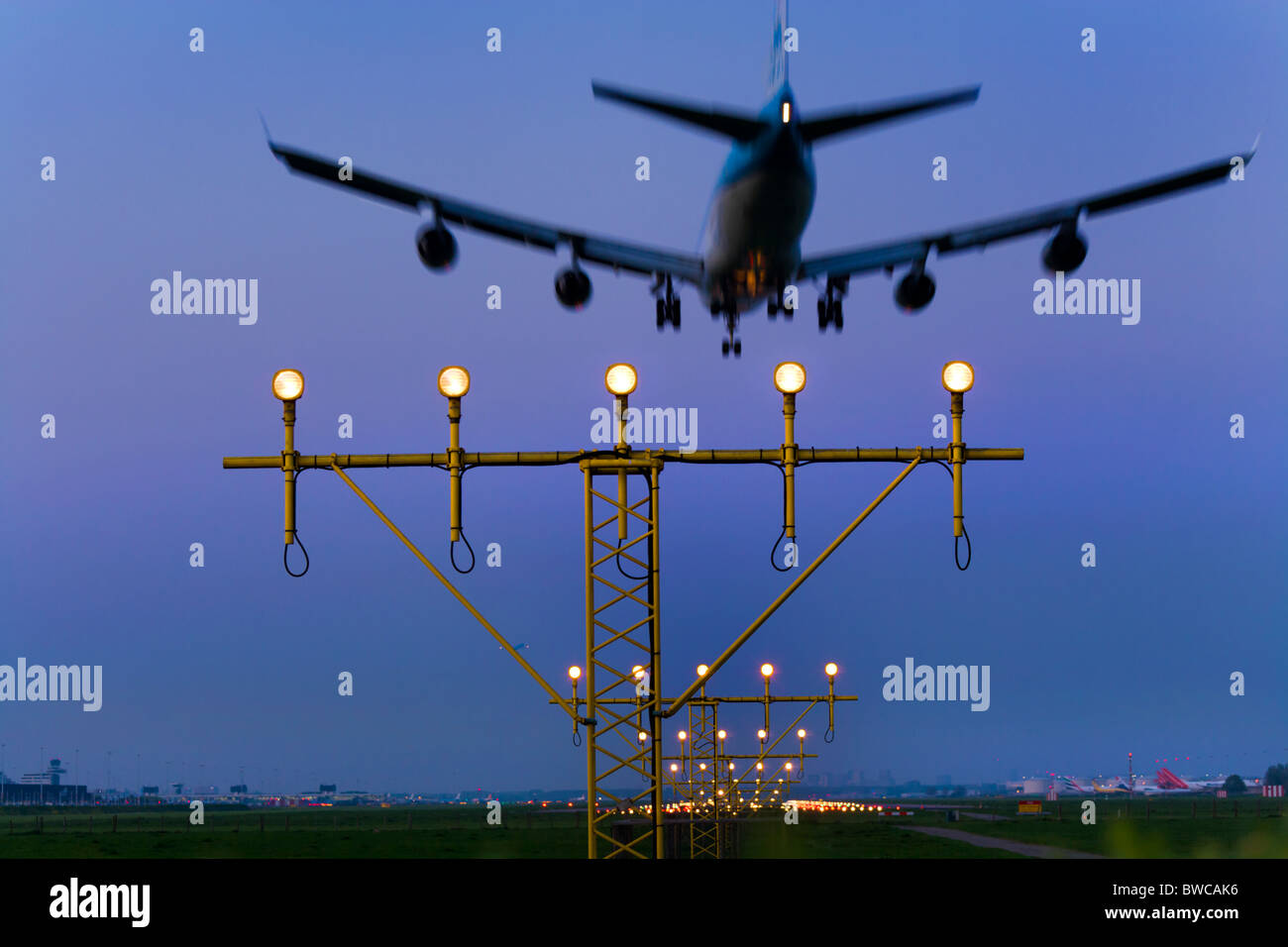KLM airplane plane approaching, landing, on the Kaagbaan runway of Amsterdam Schiphol Airport at dusk. - Stock Image