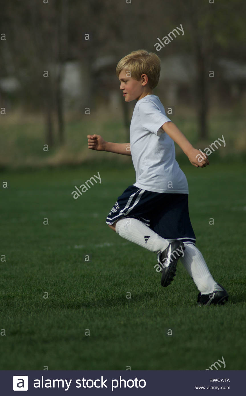 A boy runs after the ball in soccer practice - Stock Image