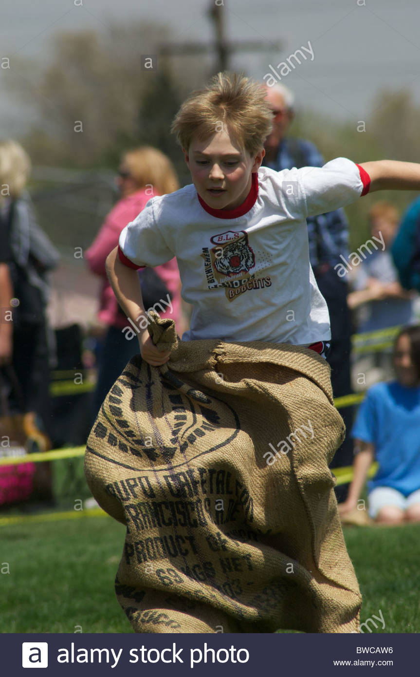 A young boy competes in a school sack hop race. - Stock Image