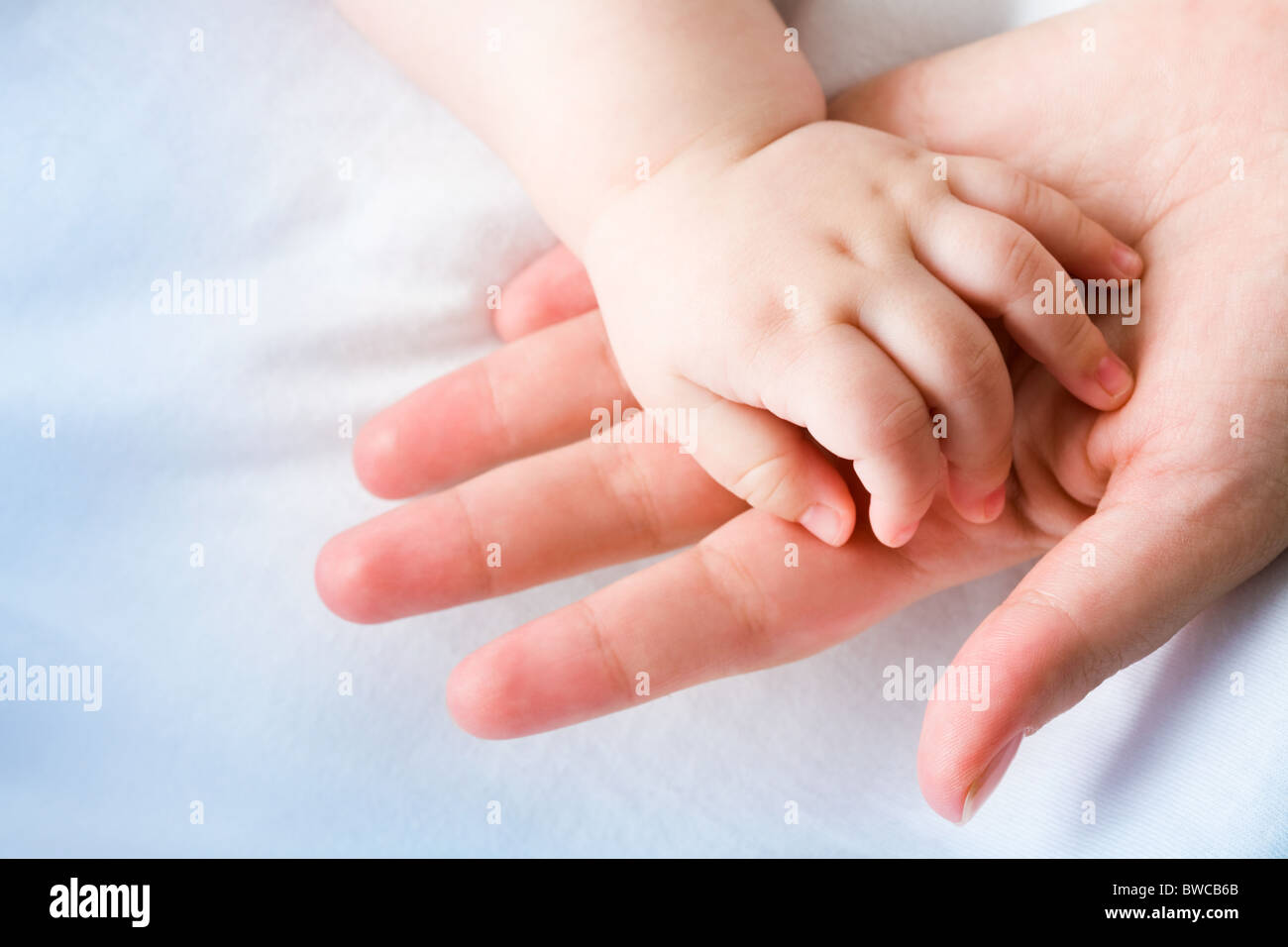 Image of mom's palm with newborn baby hand on its surface - Stock Image