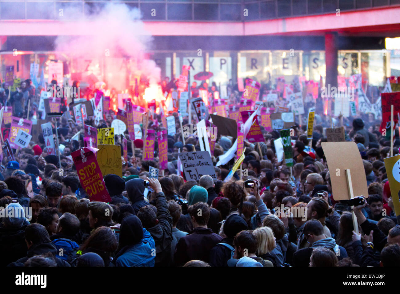 Protester lets off a flare during student protests against tuition fees - Stock Image