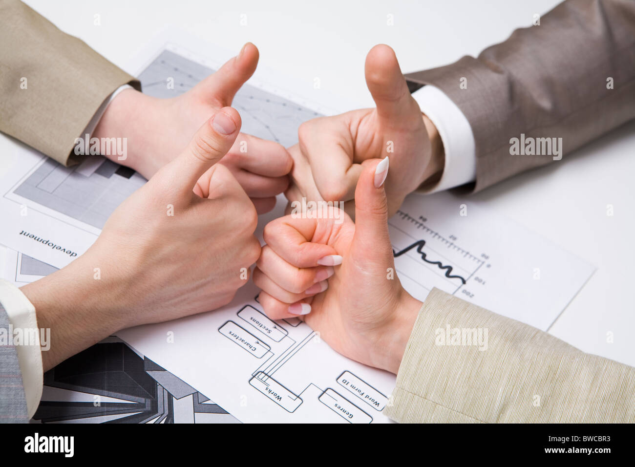 Image of human hands with their thumbs up symbolizing success in work Stock Photo