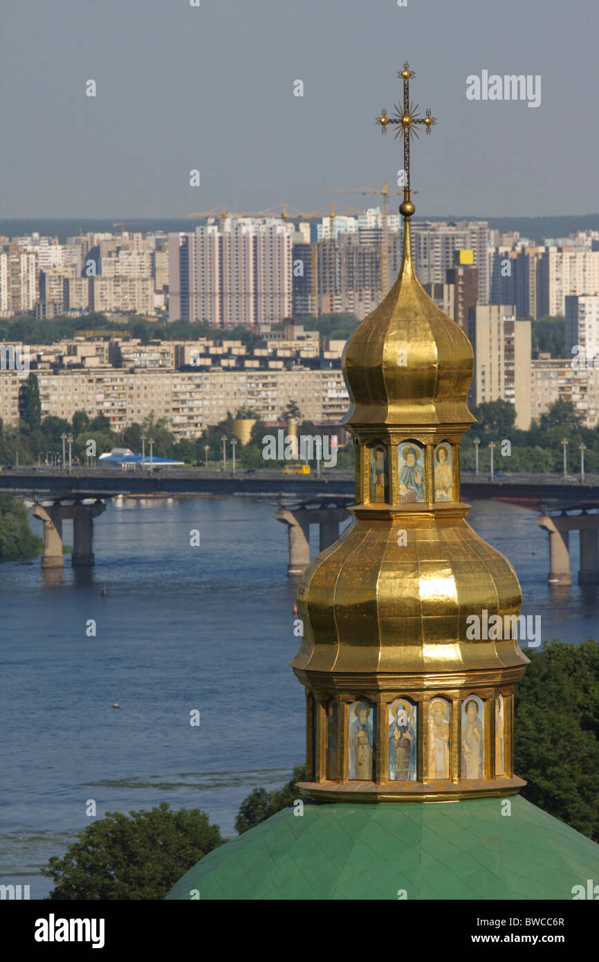 Tower of lower Lavra monastery in front of the Dnieper river and the modern skyline of Kyiv, capital of Ukraine - Stock Image
