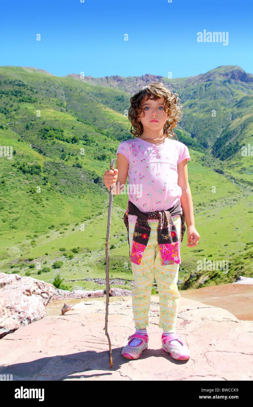 Explorer mountain girl hiker stick cane green outdoor valley landscape - Stock Image