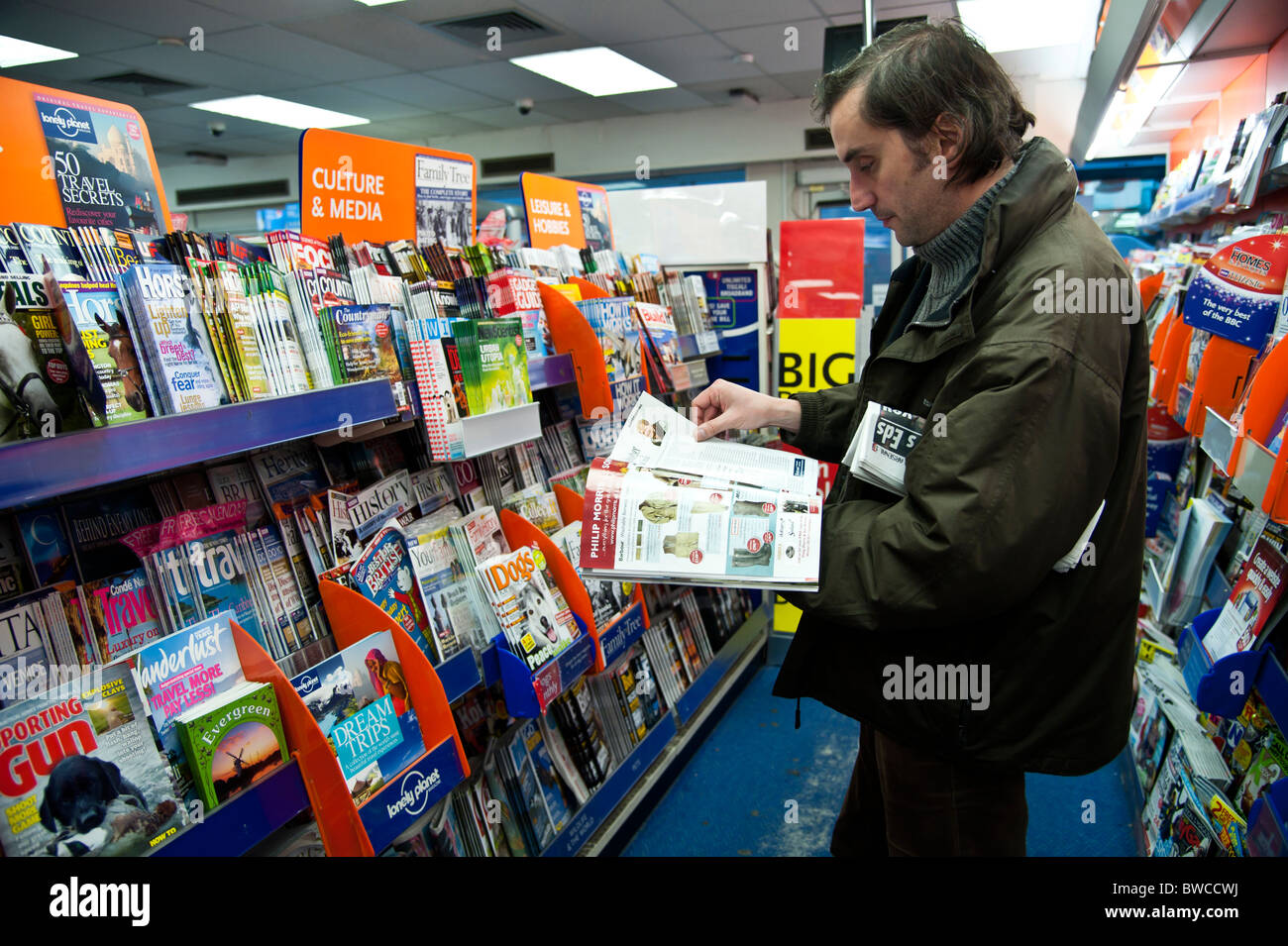 13f258faab0d A man browsing a selection of weekly and monthly magazines in a branch of  W.H.Smith newsagents UK