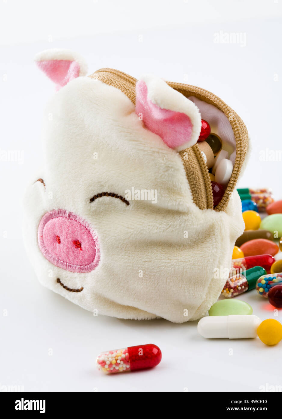 Conceptual image of a soft toy pig filled with pills and capsules symbolizing remedy of swine influenza - Stock Image