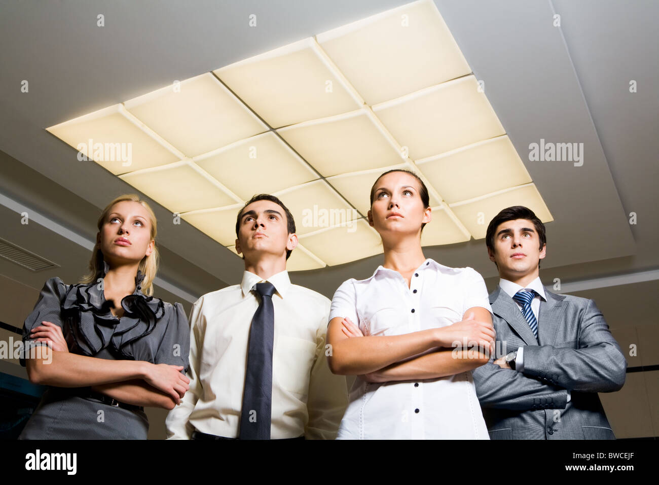 Portrait of smart associates standing in row and looking upwards seriously Stock Photo