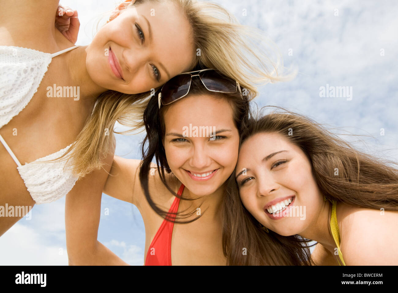 View from below of happy girls in bikini embracing each other and smiling at camera - Stock Image