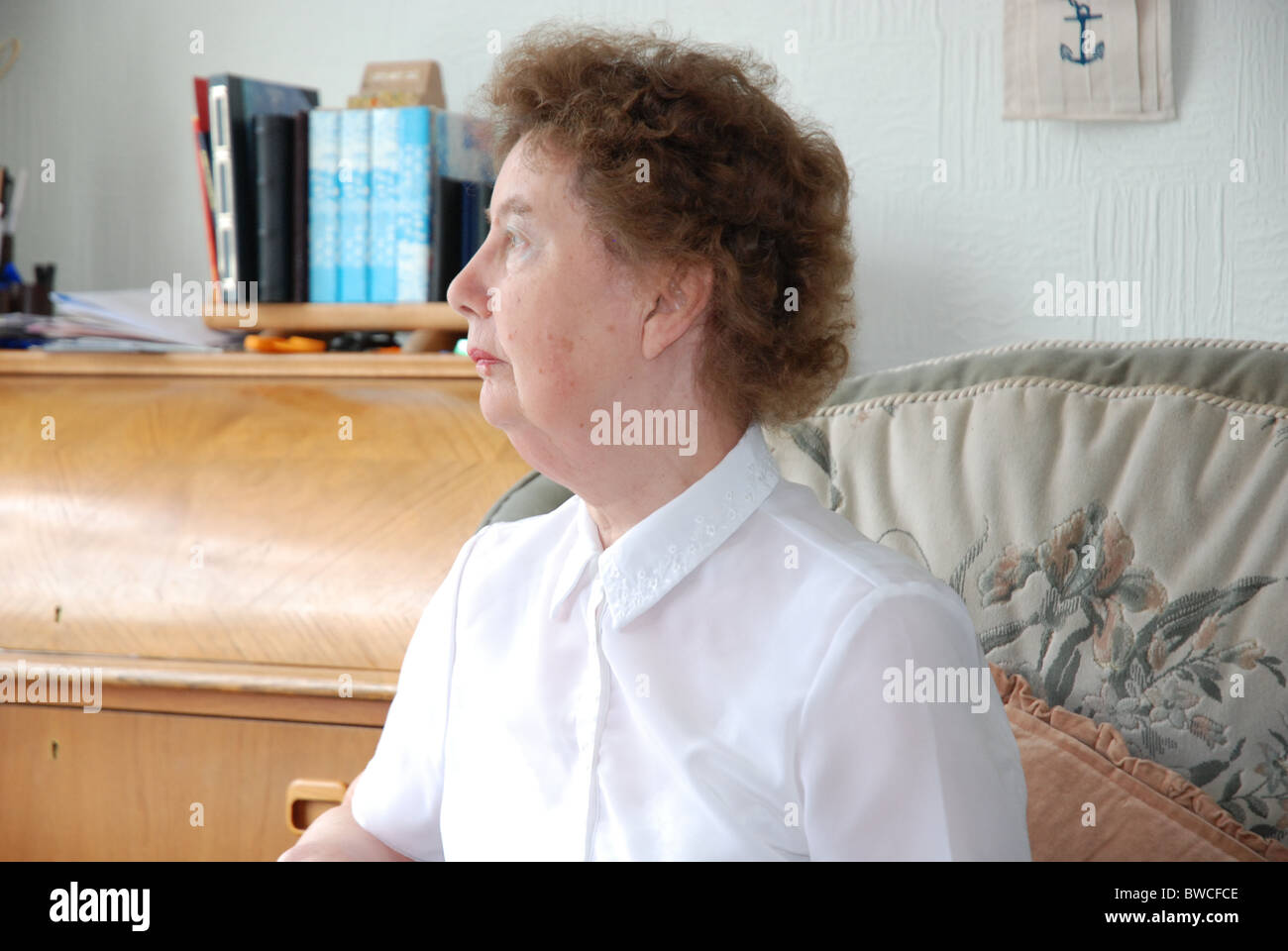 OAP lady sitting in a chair at home staring out Stock Photo