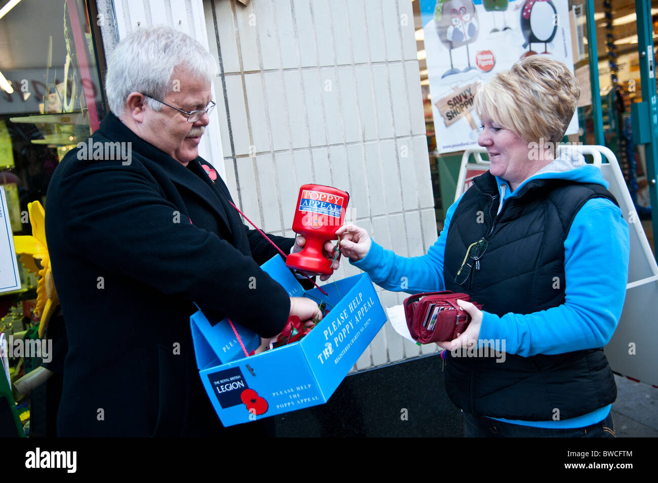 A volunteer selling Remembrance Day poppies to a woman, UK - Stock Image