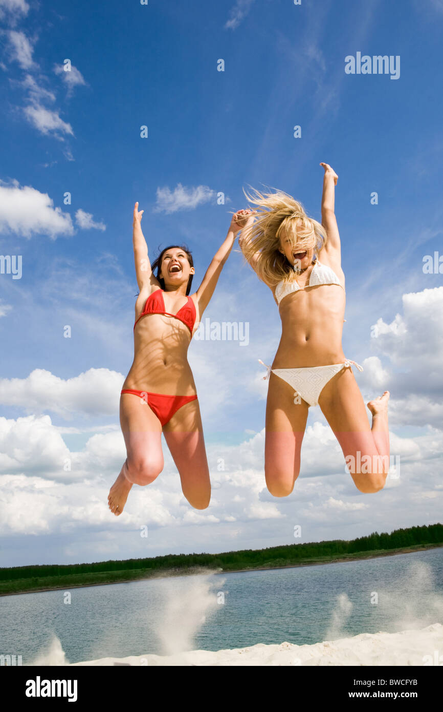Portrait of two joyful girls leaping with raised arms on background of lake on summer day - Stock Image