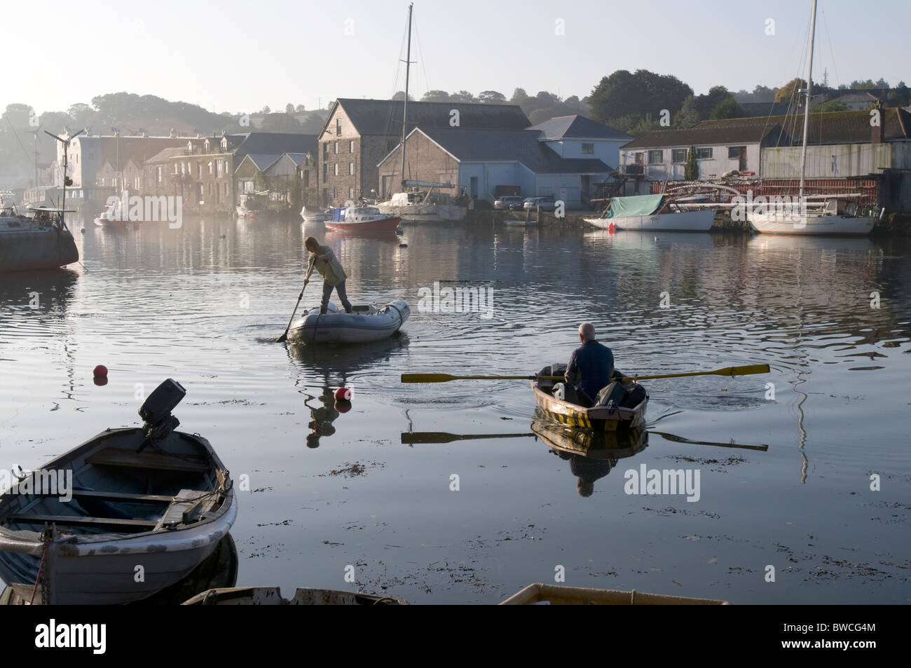 A woman paddles her dinghy on the Penryn river, Cornwall in the early morning. - Stock Image