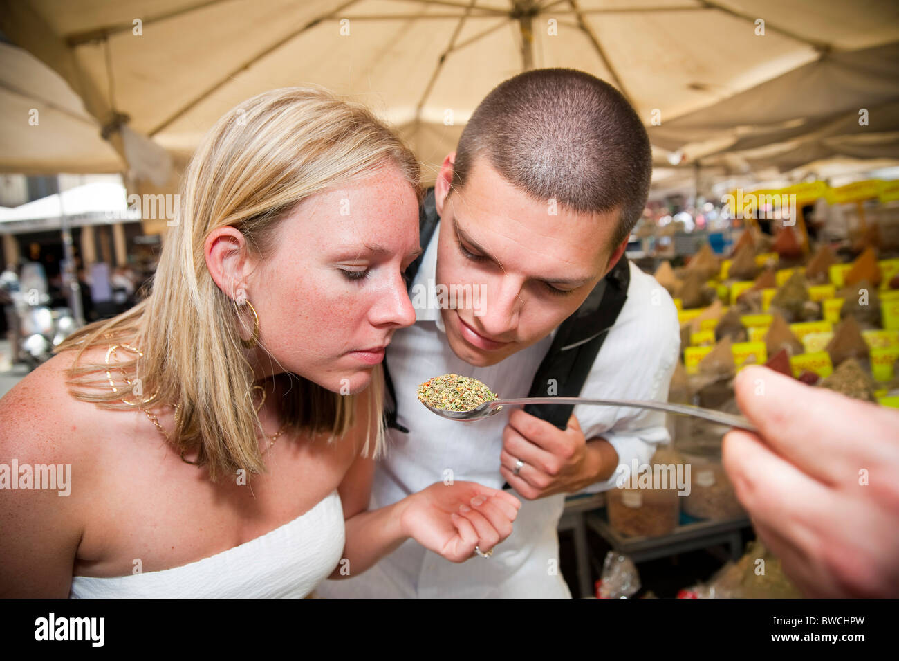 Couple smelling Italian herbs and spices - Stock Image