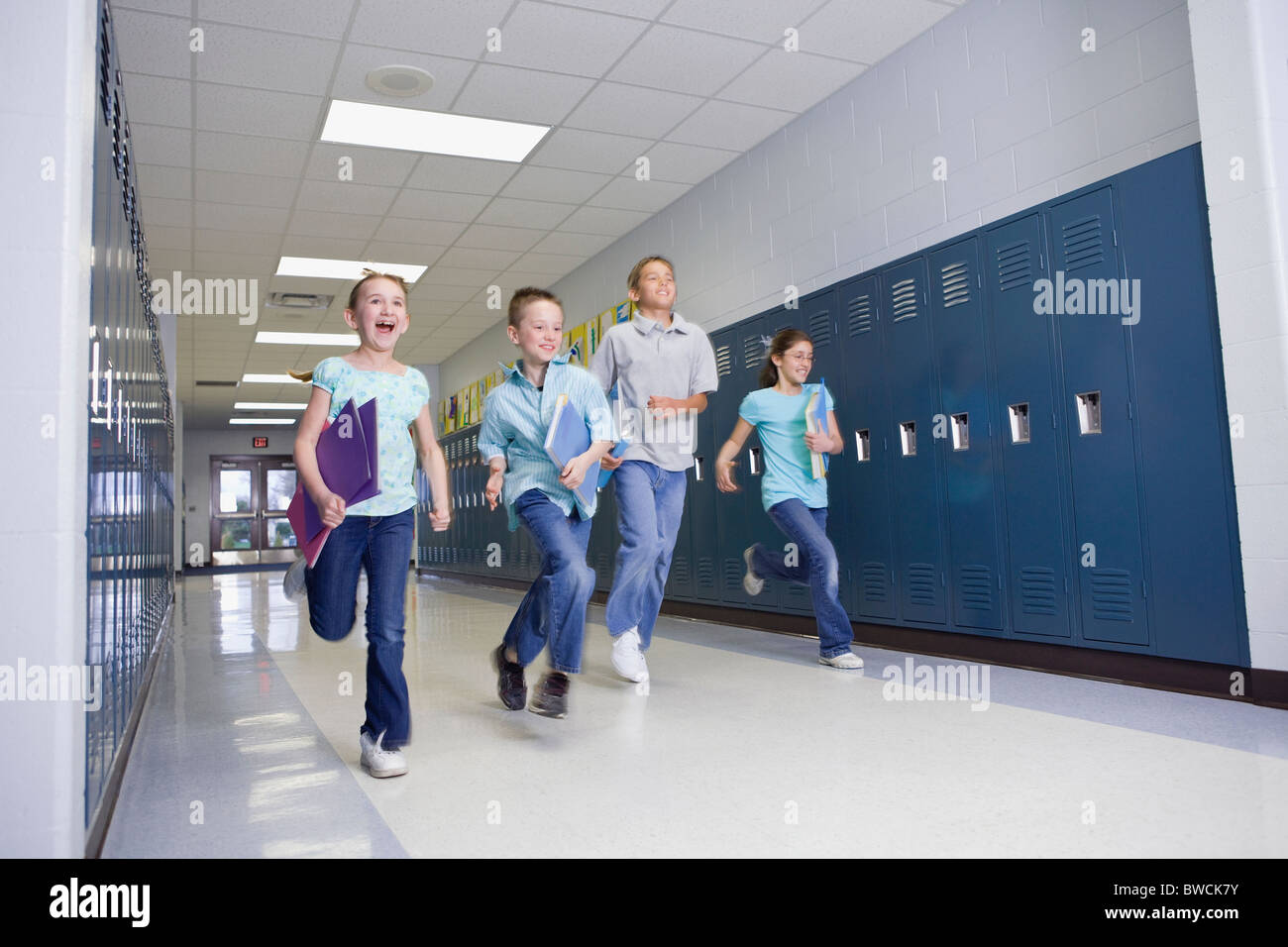 USA, Illinois, Metamora, Children (8-9, 10-11) running through school corridor - Stock Image