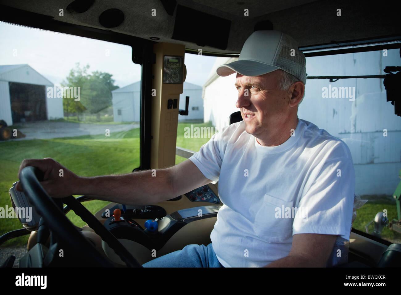 USA, Illinois, Metamora, Farmer driving tractor on farm - Stock Image