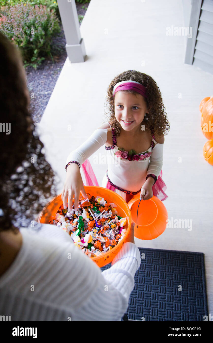 USA, Illinois, Metamora, Young woman giving candies to girl (8-9) in costume during Halloween - Stock Image