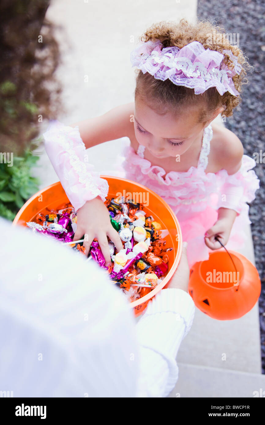 USA, Illinois, Metamora, Young woman giving candies to girl (6-7) in costume during Halloween - Stock Image