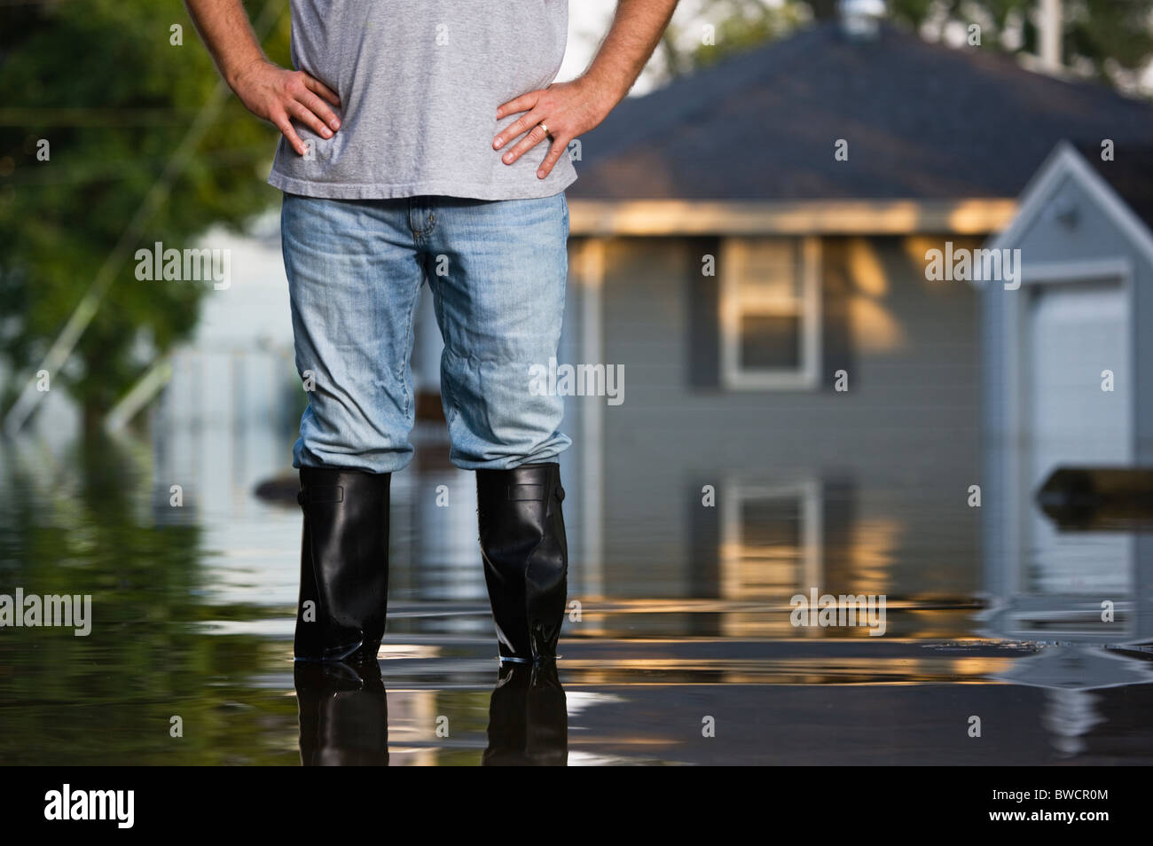 USA, Illinois, Chillicothe, Mid adult man standing in water in rubber boots, Mid section Stock Photo