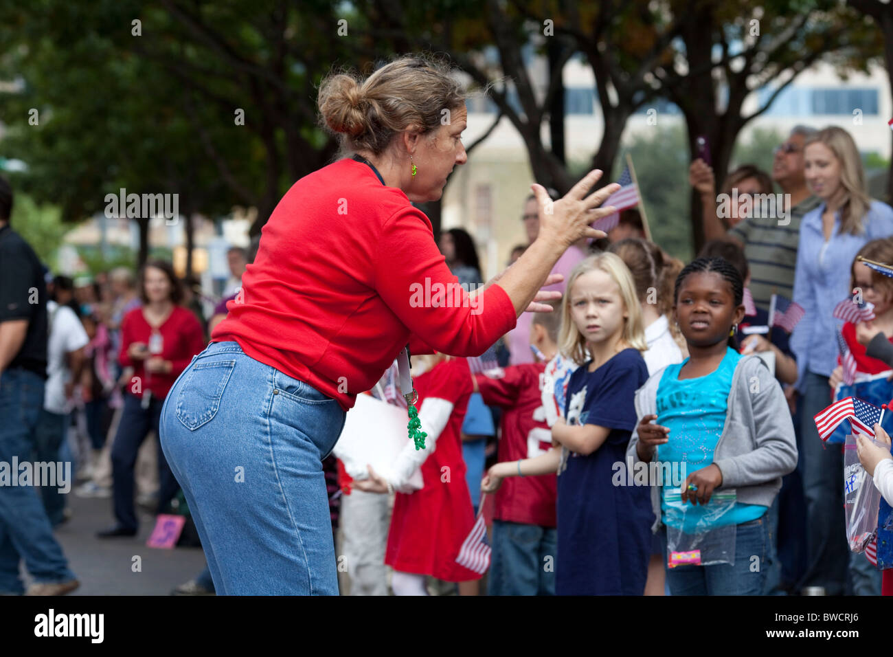 A teacher tries to prevent schoolchildren from entering the street at the annual Veteran's Day parade - Stock Image