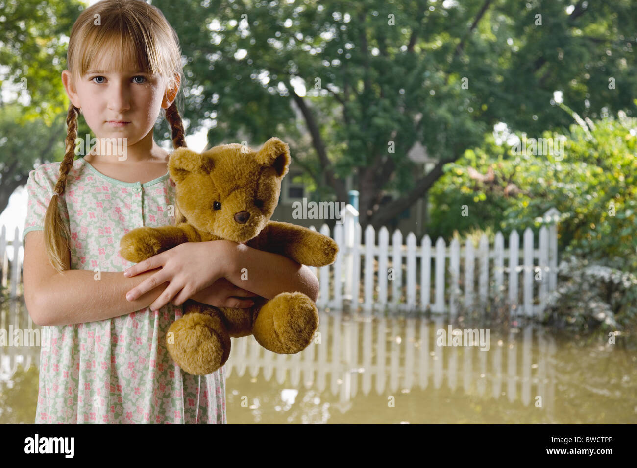 USA, Illinois, Metamora, Portrait of girl (8-9) holding teddy in flooded yard - Stock Image
