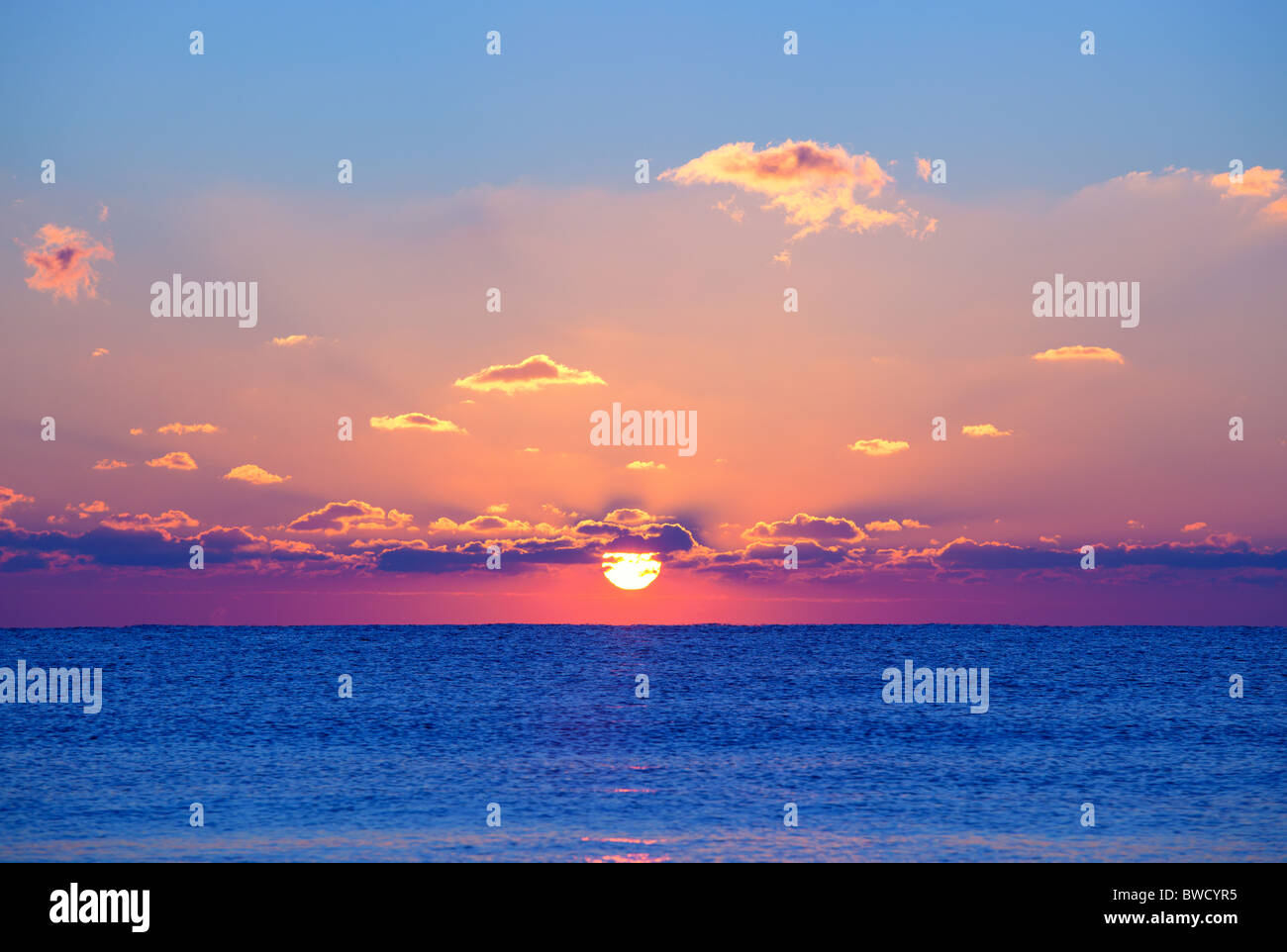 Red rising sun above the dark blue sea - Stock Image