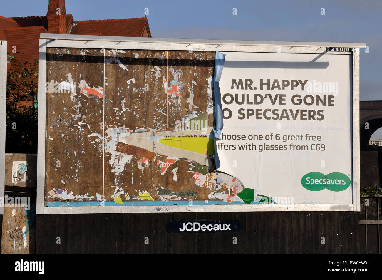 Advertising hoarding with sheets partly torn off - Stock Image