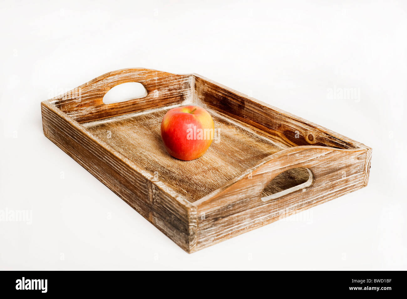 red apple on a wooden serving tray - Stock Image