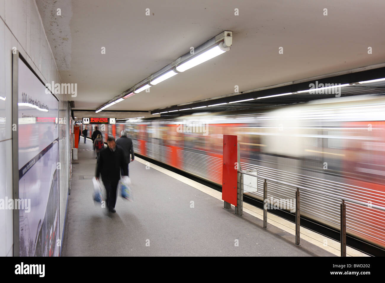 A long exposure of one of the platforms in the Rathaus U-Bahn station in Hamburg, showing moving train and people. Stock Photo