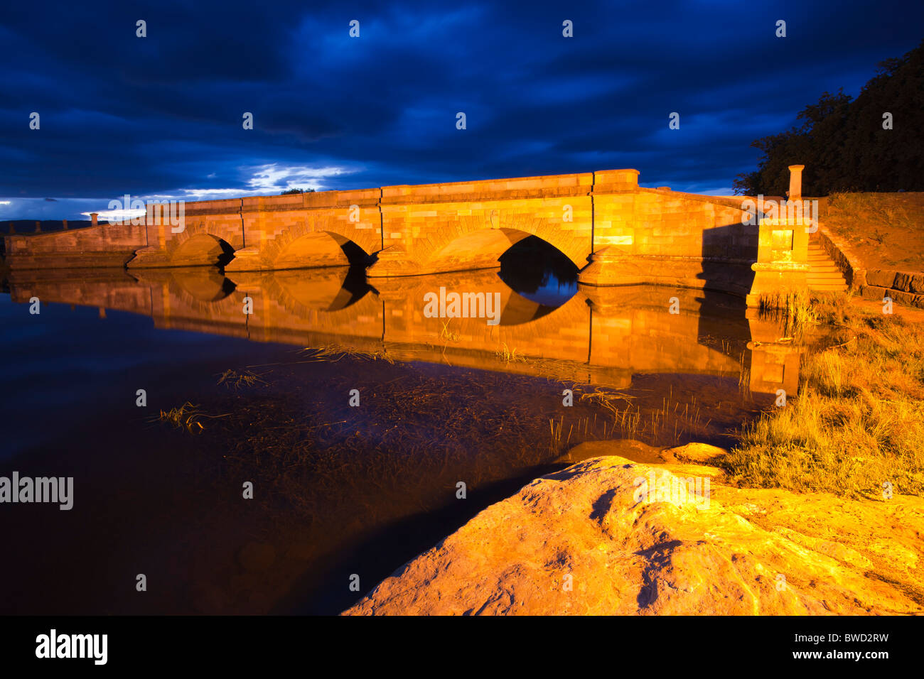The attractive convict built sandstone bridge at Ross in Central Tasmania, floodlit at night - Stock Image